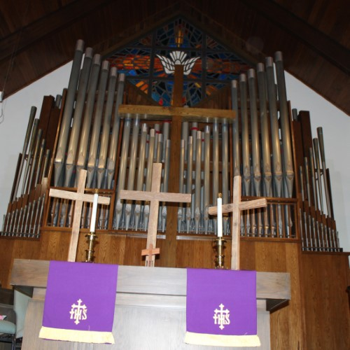 altar with 3 crosses in front of organ case